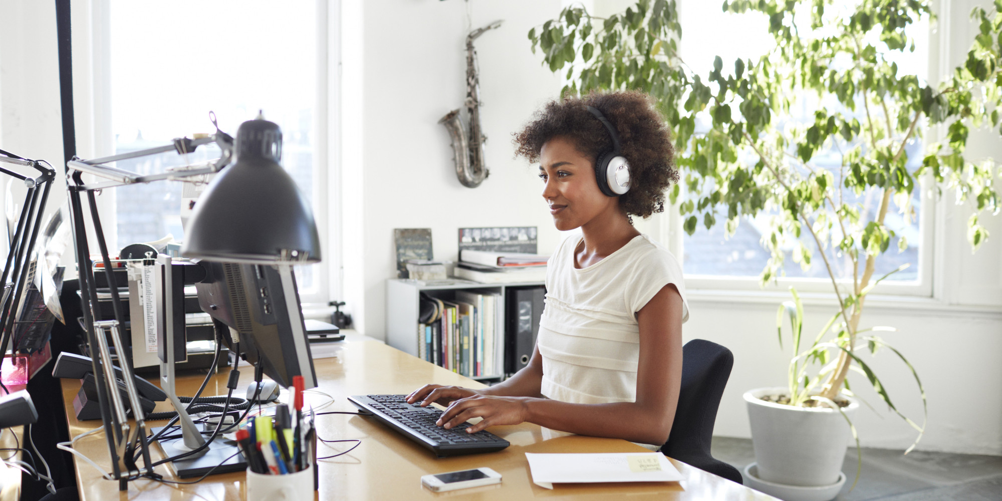Businesswoman with headphones typing on keyboard.